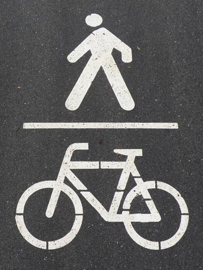 Fußgängersymbol über Fahrradsymbol, getrennt durch einen waagrechten Strich als Markierung auf dem Weg
